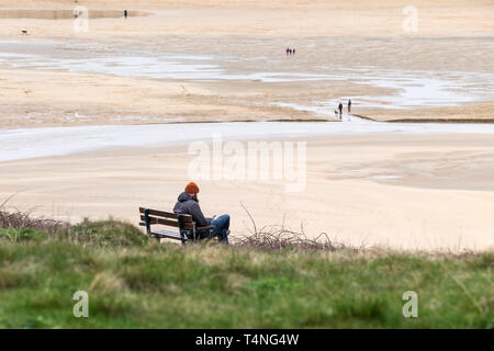 A man sitting alone on a bench overlooking Crantock Beach in Newquay in Cornwall. - Stock Image