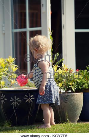 Toddler playing in garden - Stock Image