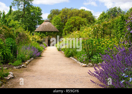 The 19th Century thatched round house surrounded by beautiful flower beds and gravel paths in the walled garden at West Dean Gardens in West Sussex - Stock Image