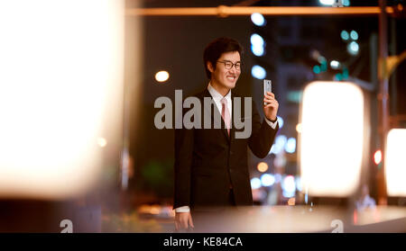 Smiling businessman holding smartphone in city at night - Stock Image