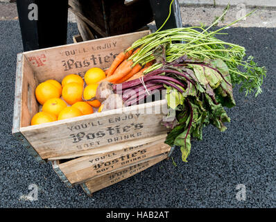 Oranges, beetroot, and carrots in wooden box 'You'll enjoy Postie's Soft Drinks' - Stock Image