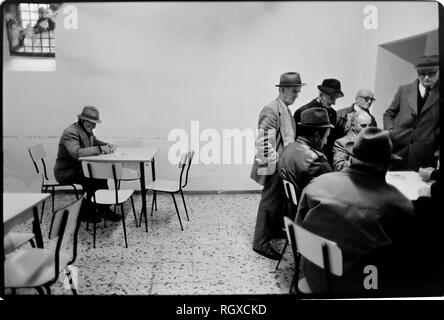 Casole d'Elsa, Tuscany, Italy. 1990. Scanned in 2019 Street and cafe bar life in the small hill top town of Casole d'Elsa in Tuscany Italy, old farmers get together to play cards in the evening in back room of local bar. - Stock Image