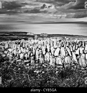Dry stone wall on the hillside above Fanore, County Clare, Ireland. View towards the Aran islands. - Stock Image