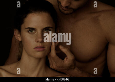 Barechested man caressing woman's cheek as she gazes at the camera - Stock Image