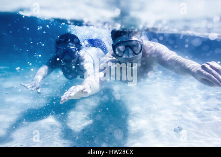 Couple swims or snorkeling underwater - Stock Image