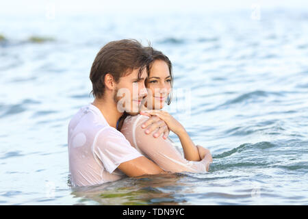 Dressed happy couple looking away bathing on the beach on summer vacation - Stock Image