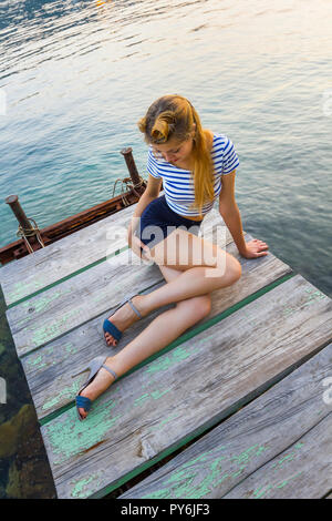 Pretty teen girl on quay view from above - Stock Image