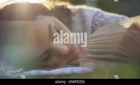 Close up selective focus of sleeping woman laying in park grass napping and reading book - Stock Image