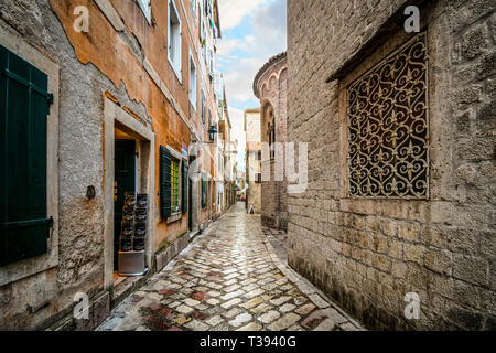 Small shops and cafes line a picturesque medieval street in the old town district of the coastal city of Kotor, Montenegro, on the Adriatic Coast. - Stock Image
