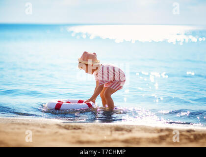 little boy playing at the beach in hat - Stock Image