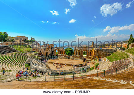 Visitors walk the ancient seating arena at the historic Greek Theatre on the Sicilian island of Taormina, Italy, with the sea,and Mt Etna in view - Stock Image