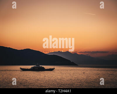 Sunset in Greece with ferry between two islands - Stock Image