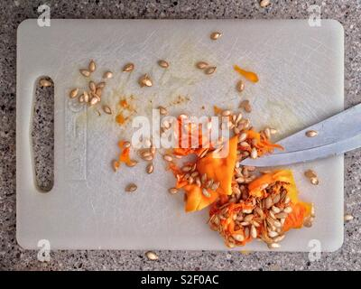 Chopping board with pulp and seeds of butternut squash with knife shot from directly above. - Stock Image