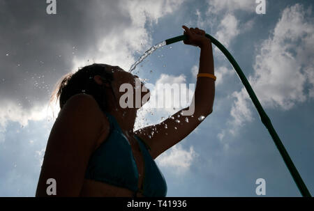Woman in a bikini holding a hosepipe over her head in the heat - Stock Image