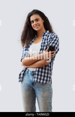 Portrait of a woman standing with arms crossed holding a mobile phone - Stock Image