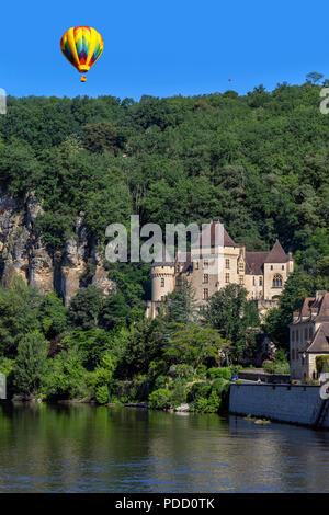 Hot air balloon above the village of La Roque-Gageac, Chateau de la Malartrie and the Dordogne River. This pictursque village is in the Dordogne depar - Stock Image