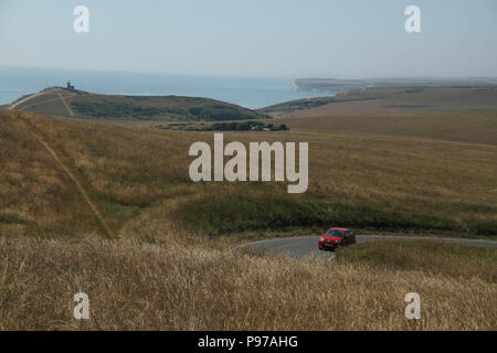 Beachy Head, UK - July 14 2018: A road cuts through the Eastbourne Downland Estate grasslands by the hilltop of the chalk sea cliff at Beachy head on a hot summers day on 14 July 2018. Temperatures rose to 27 degrees and is expected to stay high for another month. The cliff, the highest chalk sea cliff in Britain rises to 162 metres above sea level and unfortunately one of the most notorious suicide spots in the world. Credit: David Mbiyu - Stock Image