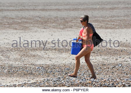 Littlehampton, UK. Monday 2nd July 2018. A woman walks on the beach on another very warm and humid morning in Littlehampton, on the South Coast. Credit: Geoff Smith / Alamy Live News. - Stock Image