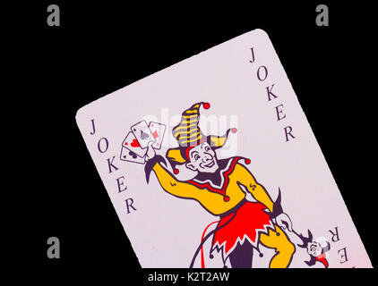 A Joker playing card set against a black background - Stock Image