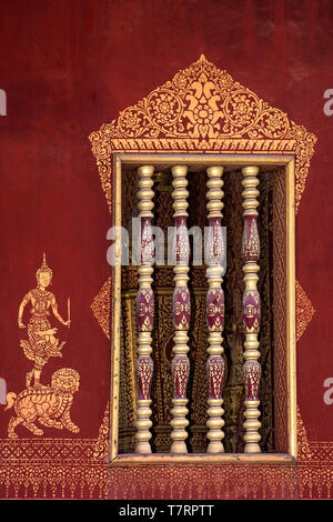 Windows accented with Khmer-style wooden balustrades and gilded murals stencils of a deity, standing on a lion, Wat Sensoukharam,  Luang Prabang, Laos - Stock Image