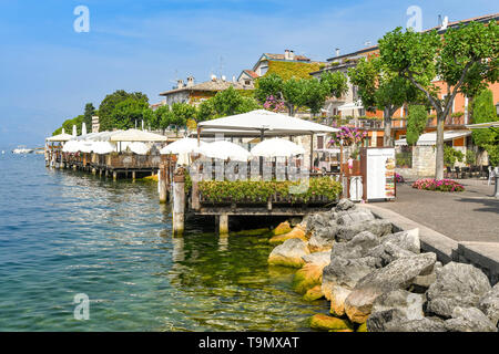 TORRI DEL BENACO, LAKE GARDA, ITALY - SEPTEMBER 2018: Outdoor dining areas with sun canopies at restaurants on the promenade on the edge of Lake Garda - Stock Image