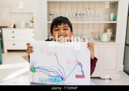 Portrait enthusiastic boy showing drawing - Stock Image