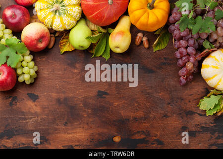 Autumn backdrop with pumpkins, apples, pears, grapes and colorful leaves over wooden background. Top view with space for your text - Stock Image