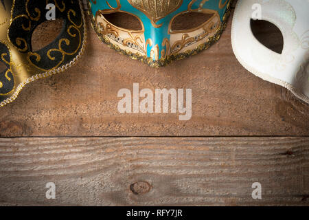 Three venetian carnival masks for mardi gras parade on wooden table - Stock Image