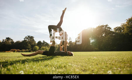 Strong young couple doing acroyoga workout. Man and woman in park practising pair yoga in morning. - Stock Image