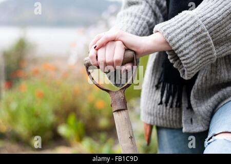 Cropped shot of womans hands digging organic garden with fork - Stock Image