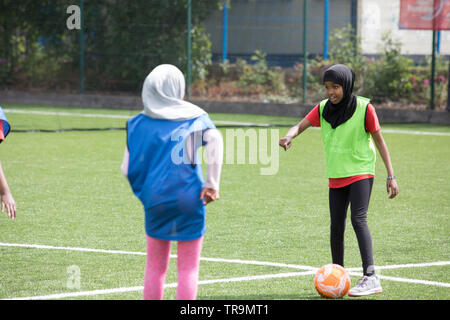 Muslim girls playing football on an astroturf training pitch. Some are wearing hijabs (headscarves). - Stock Image
