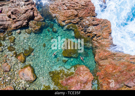 Aerial view of two children swimming in an ocean rock pool, Australia - Stock Image
