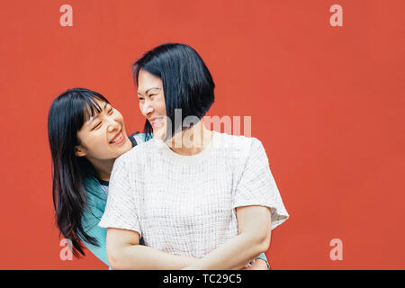 Asian mother and daughter embracing outdoor - Happy Chinese family enjoying time together outside - Parenthood, love and people lifestyle concept - Stock Image