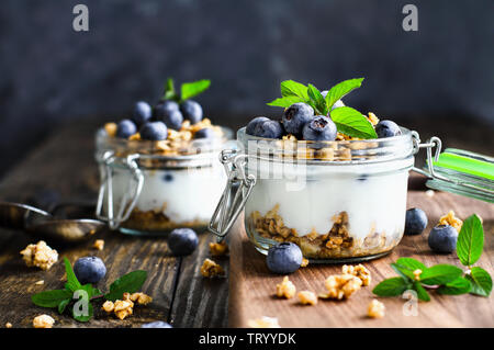 Healthy breakfast of blueberry parfaits made with fresh fruit, Greek yogurt, granola and mint leaves over a rustic cutting board and table. Selective - Stock Image