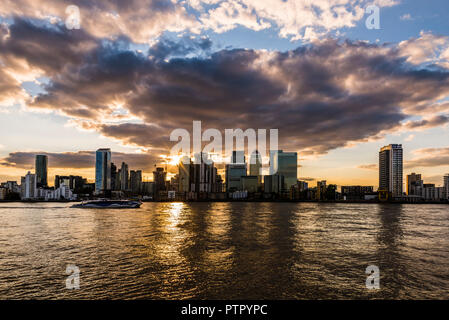 Sunset and boat over the River Thames and Canary Wharf, London Docklands, London, UK - Stock Image
