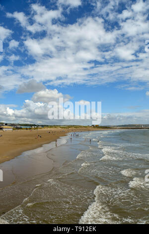 Coney Beach in Porthcawl at low tide, with waves lapping the beach. It is a traditional seaside resort on the South Wales coast - Stock Image