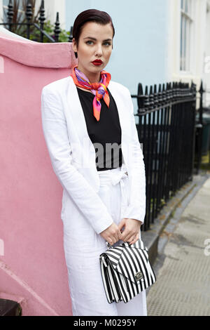 Women in white suit leaning against pink wall in street - Stock Image