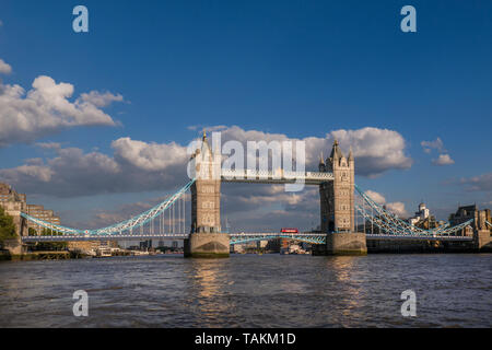 Tower Bridge wide view landscape with London red bus crossing bridge and The River Thames, viewed from a RB1 Commuter River Boat in late afternoon sun. Southwark London UK Panorama Vista City View attraction with clear blue sky. Tower Bridge is a combined bascule and suspension bridge in London, built between 1886 and 1894. The bridge crosses the River Thames close to the Tower of London and has become an iconic and enduring symbol of London England Great Britain UK - Stock Image