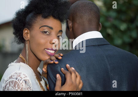Loving couple standing out with the woman's head on his man's shoulder. - Stock Image