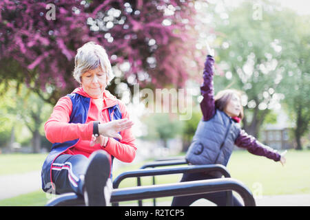 Active senior female runner stretching leg and checking smart watch - Stock Image