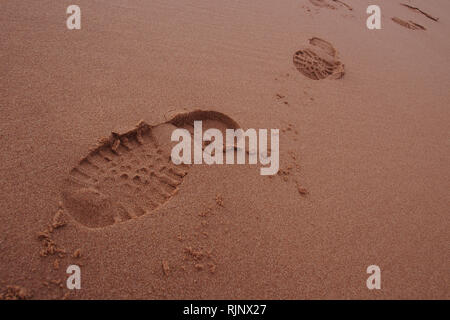 Walking boot prints in damp sand on a sandy beach approaching the  foreground of the picture - Stock Image
