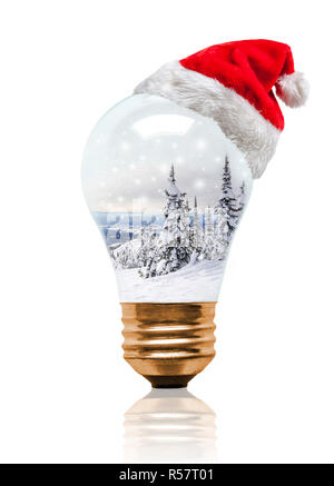 Snow globe light bulb wearing Santa hat with Christmas Winter scene with copy space. Glowing Xmas season and bright New Year. - Stock Image