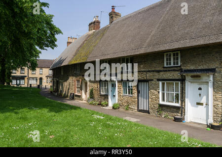 Row of old terraced thatched cottages overlooking the village green, Harrold, Bedfordshire, UK - Stock Image