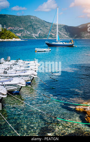 Small tourist boats for rent docked on the shore. Turquoise bay, crystal clear water. Amazing summer vacation on mediterranean island. - Stock Image