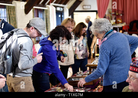 People perusing cutlery items at an Antique, Vintage and Craft Fair, Chawton, near Alton, Hampshire, UK. 24 February 2019. - Stock Image