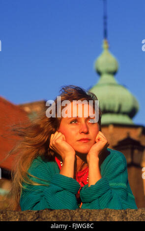 Healthy and happy looking  woman wearing colorful sweater in front of wall with church steeple in Stockholm - Stock Image