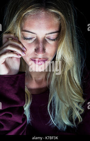 Young woman looking down sadly, portrait - Stock Image