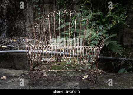 An old rusty, once white, metal bench that has seen its best days. - Stock Image