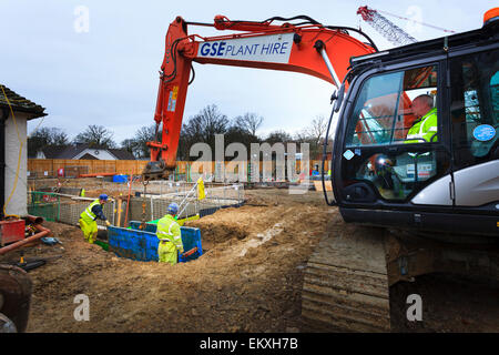 Mobile crane placing metal shoring to trench. - Stock Image