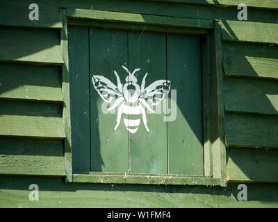 Green Beekeeping Hut with White Bee Logo, South Stoke, Oxfordshire, England, UK, GB. - Stock Image